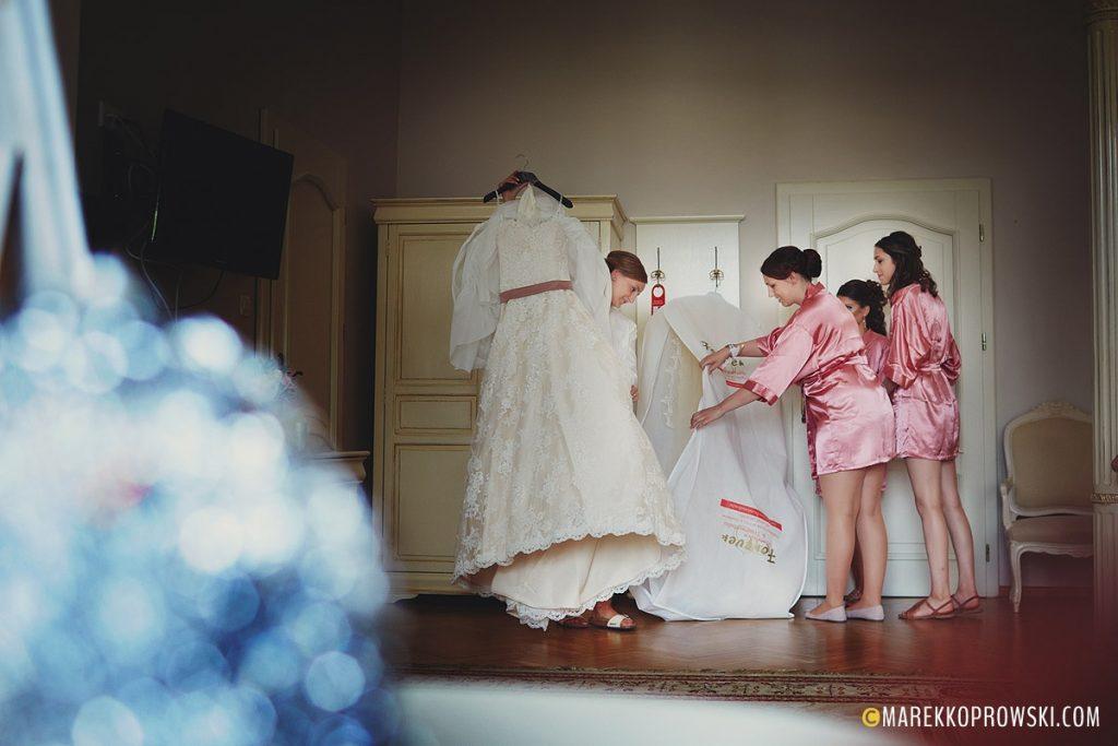 Druhny pomagają pannie młodej ubrać suknię