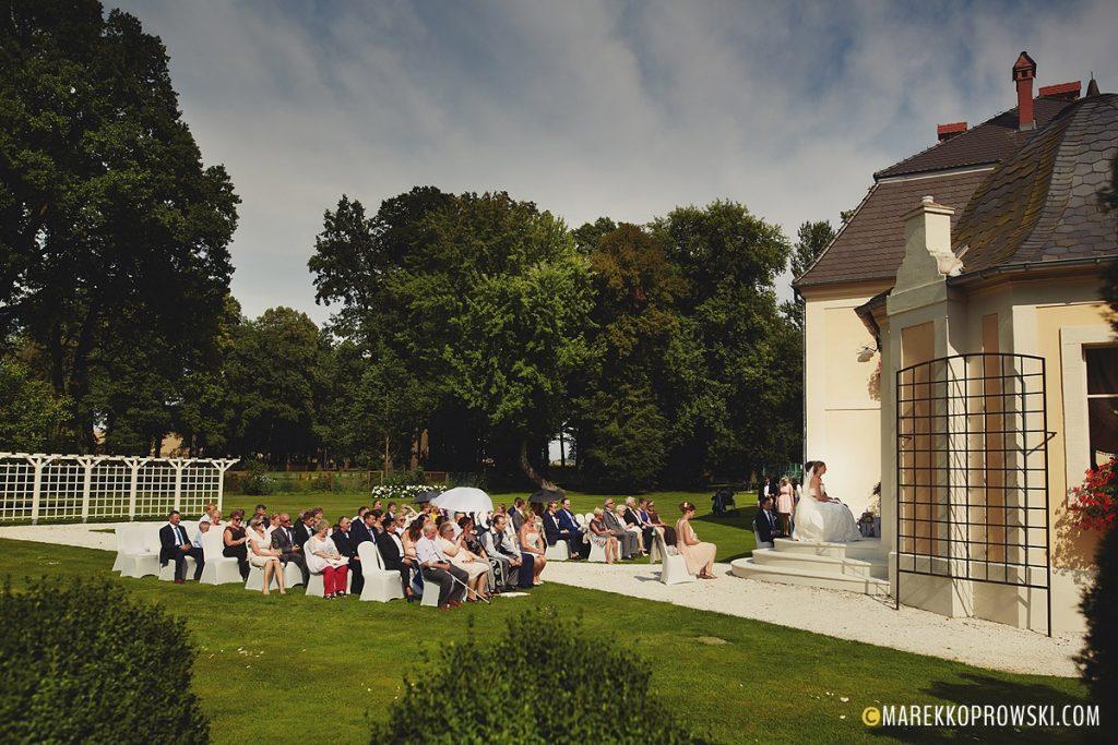 Ślub w plenerze - widok na gości, tereny zielone i budynek