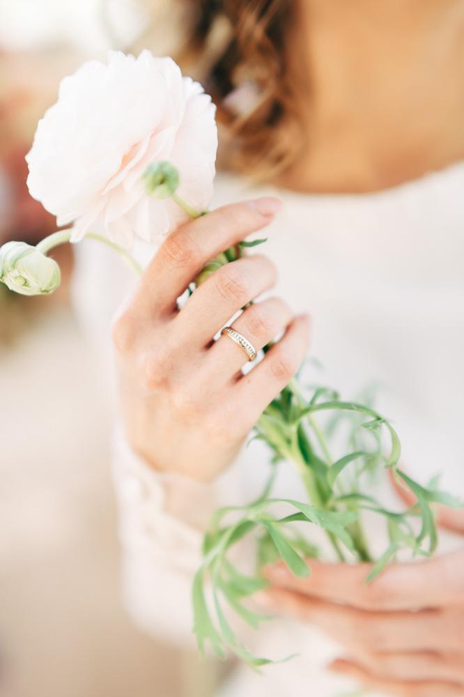 obrączka ślubna i bladoróżowy jaskier